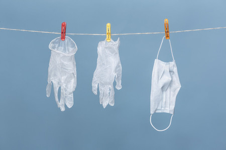 Protective gloves and face mask hanging from clothesline