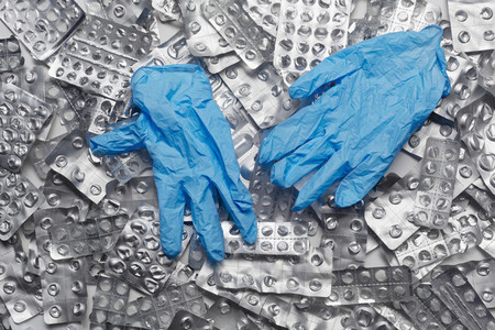 Protective rubber gloves on pile of blister packs