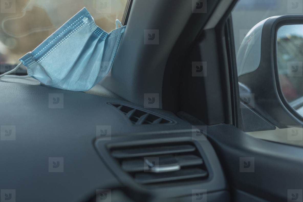 Protective face mask on dashboard of car