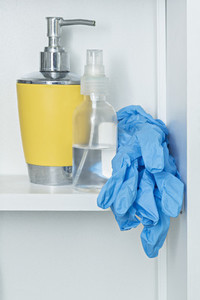 Protective gloves on bathroom shelf with soap and disinfectant