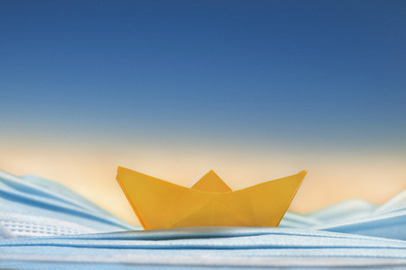 Yellow origami boat on blue disposable face mask