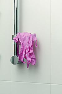 Pink protective gloves hanging on shower handle