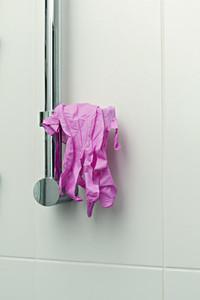 Pink protective gloves hanging on shower handle
