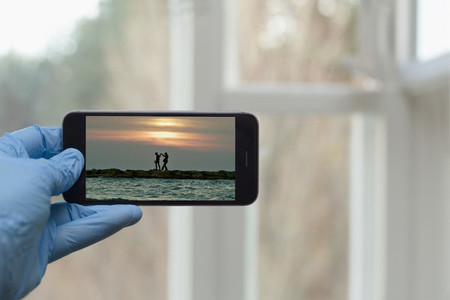 POV Hand in protective glove looking at travel photo on smart phone screen
