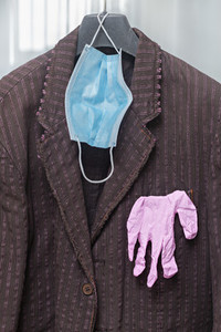 Protective face mask and gloves hanging on suit jacket