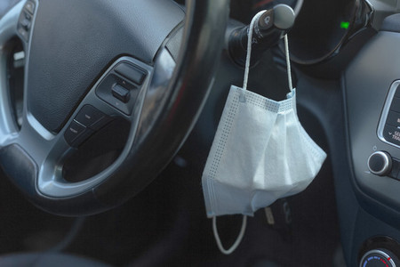 Protective face mask hanging from car steering wheel