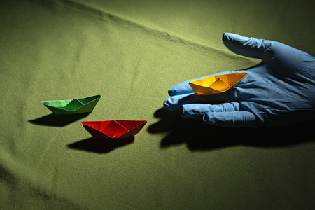 Hand in protective glove holding origami boat