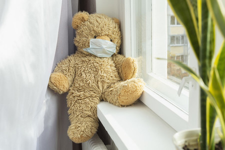 Cute teddy bear in protective face mask on windowsill
