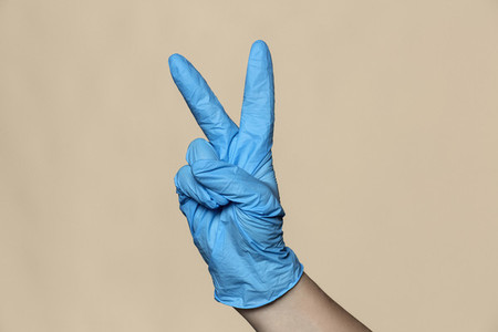 Hand in protective glove gesturing peace sign