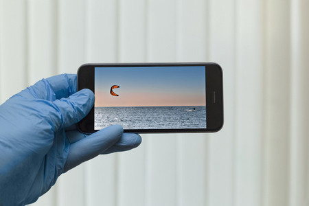 POV Gloved hand looking at kite surfing photo on smart phone screen