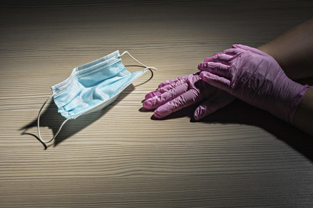 Gloved hands next to disposable protective face mask