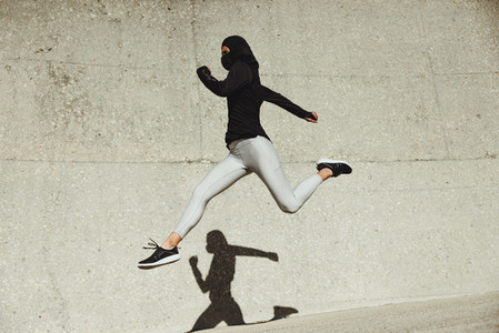 Woman running and jumping in sportswear