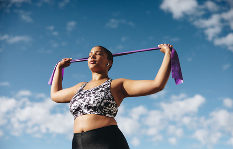 Healthy woman exercising with resistance band