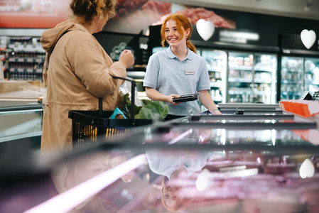 Grocery shop assistant helping customer
