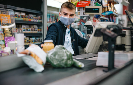 Supermarket checkout employee with face mask