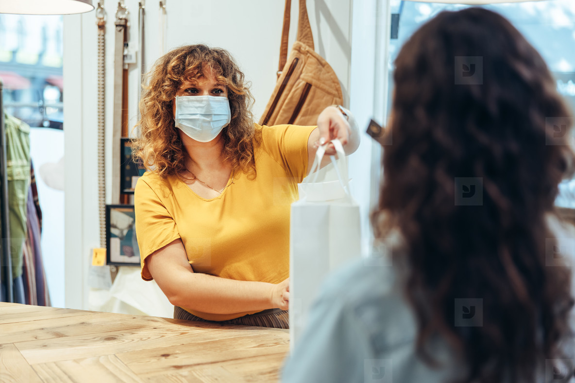Clothing store owner with face mask assisting customer