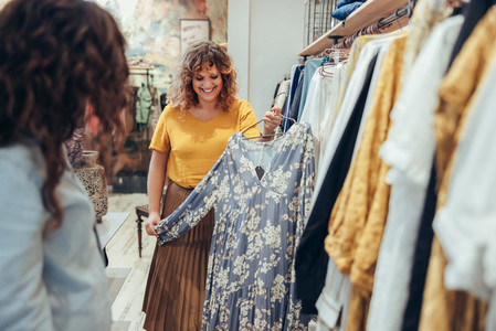 Shop assistant showing dress to female customer