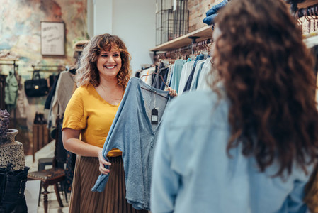 Saleswoman assisting customer in clothing store