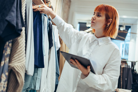Woman taking clothes stock in her store