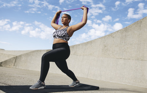 Plus size woman exercising with resistance band