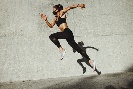 Fitness woman sprinting wearing face mask