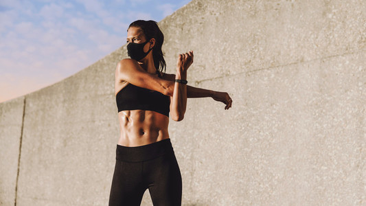 Woman with face mask doing warm up workout