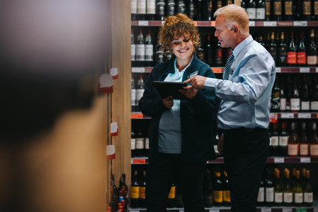 Supermarket employees taking inventory of liquor section