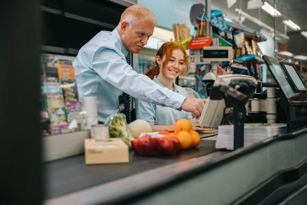 Senior manager training new cashier at supermarket