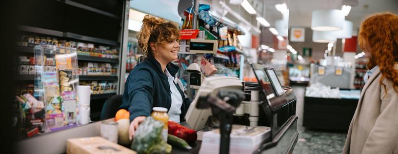 Cashier assisting customer at supermarket checkout
