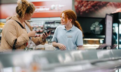Grocery store worker helping female customer