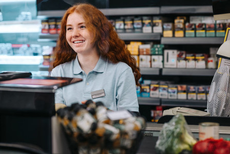 Woman working at supermarket checkout counter