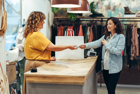 Female customer paying for the purchase at clothing store