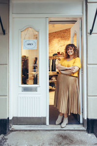 Businesswoman standing at entrance of her store