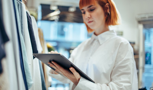 Businesswoman using digital tablet in her clothing store