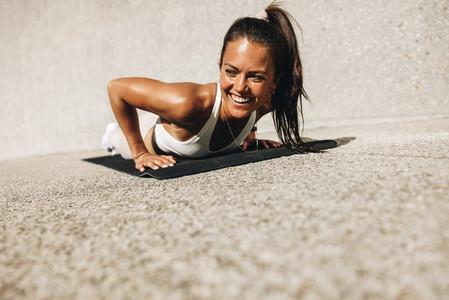 Smiling woman doing push ups on exercise mat