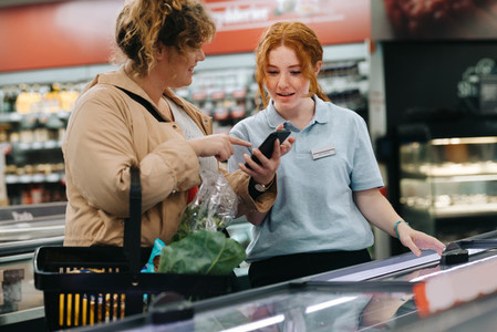 Shopper taking help of a store assistant at supermarket