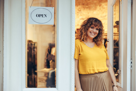 Businesswoman leaning to the doorway of her fashion store