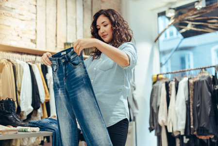 Woman shopping jeans in a clothing store