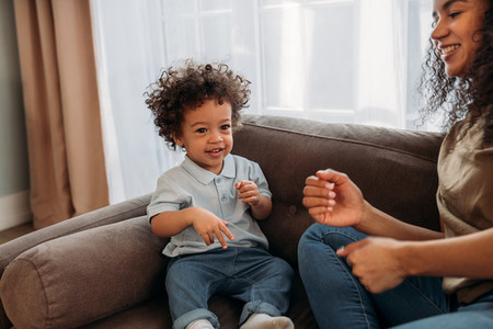 Smiling woman playing with her little son on sofa