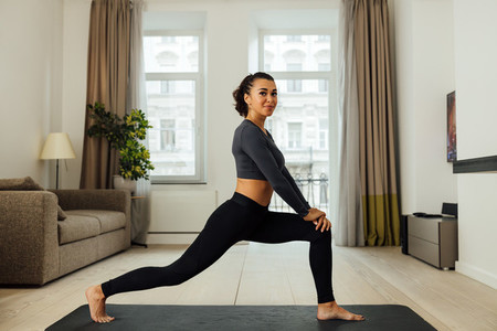 Smiling woman stretching her legs on a mat