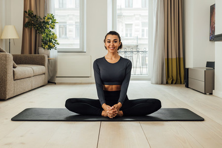 Beautiful smiling woman sitting on a mat at home
