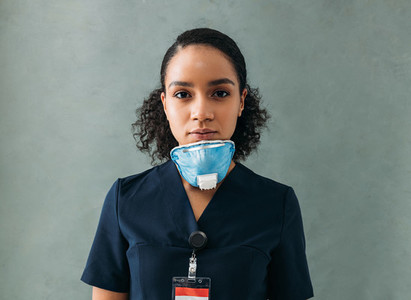Female doctor with a medical mask under her chin  Woman in uniform standing at wall