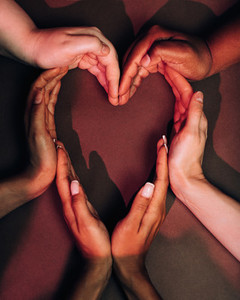 Shot from above of female hands making a big heart shape