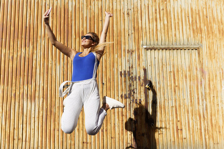 Girl jumping while making a selfie with her smartphone