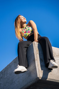 Funny young girl sitting on urban wall