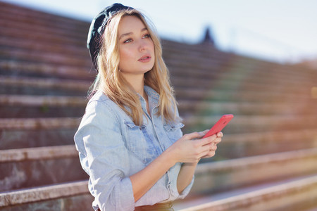 Blonde woman using a smartphone sitting on some city steps  wearing a denim shirt and black beret