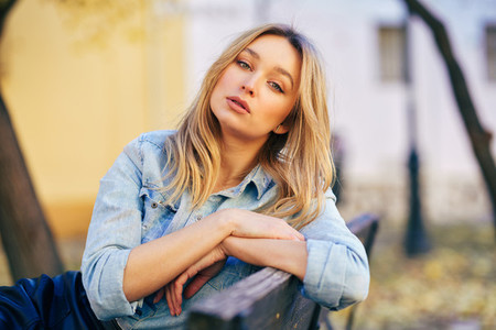 Blonde woman wearing denim shirt and black leather skirt sitting in an urban bench