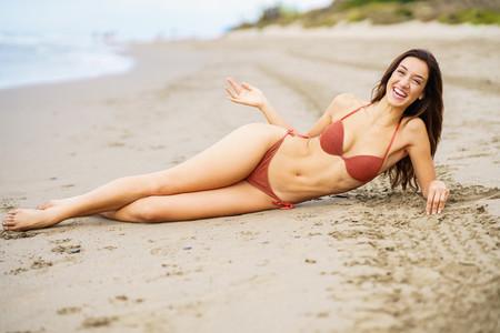Woman with beautiful body laughing on a tropical beach wearing bikini