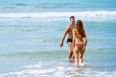Young couple bathing together on the beach enjoying their holiday at sea