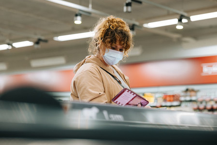 Woman with face mask shopping grocery at store